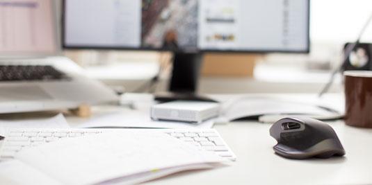 Schreibtisch mit Tastatur und Maus im Vordergrund, Bildschirm im Hintergrund