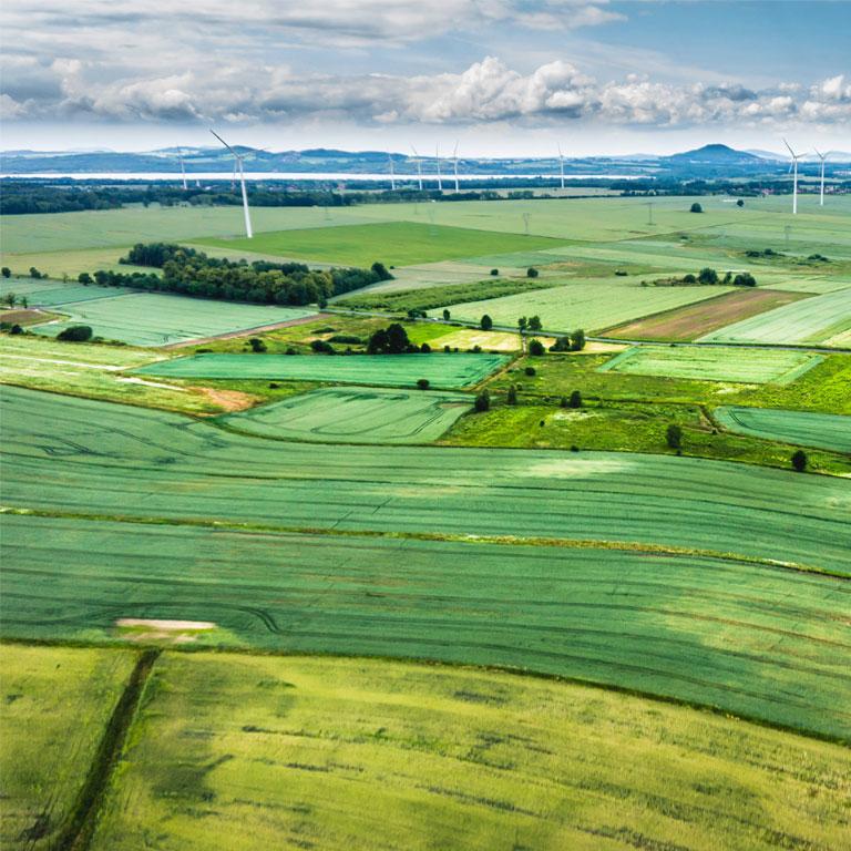 grüne Sicht auf Windräder, ökologische Felder, Berge und Wasser