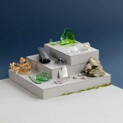 Podest mit Rohstoffen: Glas, Stein, Blei, Holz, Moos, Kunststoff, Metall